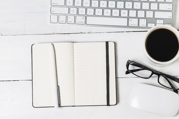 Leere papierkram vorlage für designer. responsive design mockup auf vintage holz hintergrund. papier, briefkopf, kaffeetasse, smartphone, bleistift und kopfhörer auf holztisch hintergrund. draufsicht