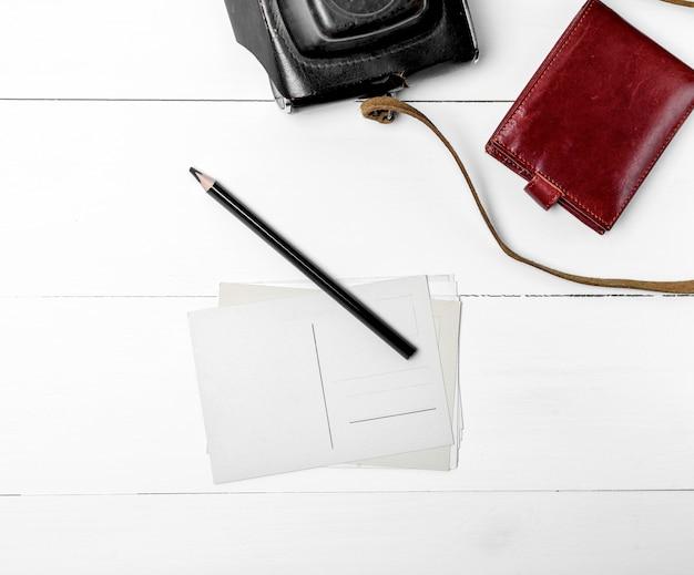 Leere papierpostkarten und ein schwarzer hölzerner bleistift auf einem weißen hölzernen hintergrund, neben einem braunen ledernen geldbeutel