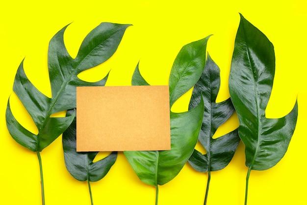 Leere papierseite auf monstera deliciosa liebm blätter auf gelbem hintergrund.