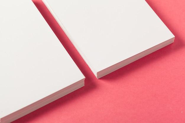 Leere papierstücke auf einem farbigen rosa hintergrund