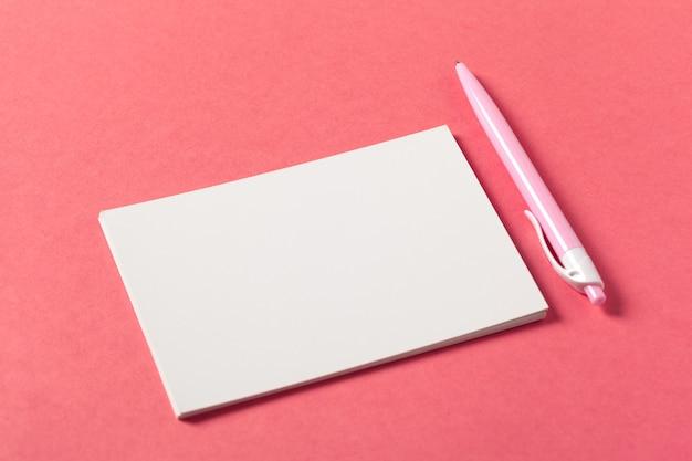 Leere papierstücke auf einem farbigen rosa