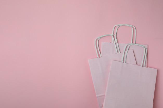 Leere papiertüten auf rosa hintergrund, platz für text