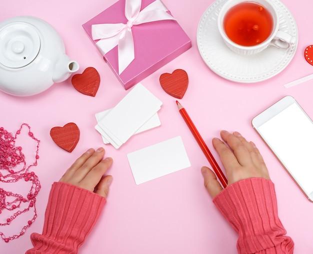 Leere papiervisitenkarten und ein roter bleistift, nahe bei zwei händen der frauen
