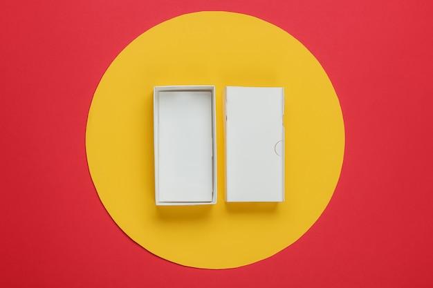 Leere pappschachtel von einem modernen smartphone auf rot mit gelbem kreis in der mitte