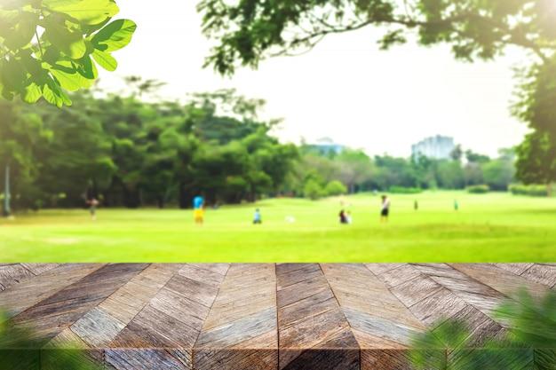 Leere plankentischplatte des schmutzes hölzerne mit unschärfepark-grünnatur bokeh und blattvordergrund