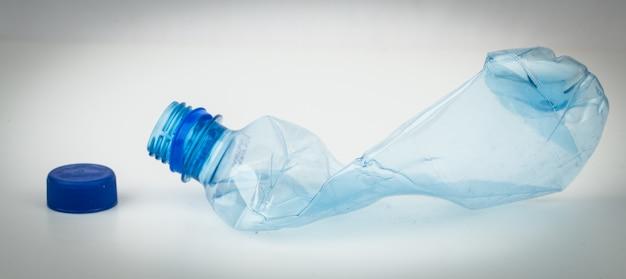 Leere plastikflasche zerquetscht und blaue kappe