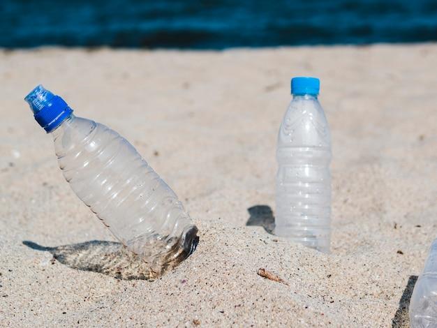 Leere plastikwasserflasche auf sand am strand