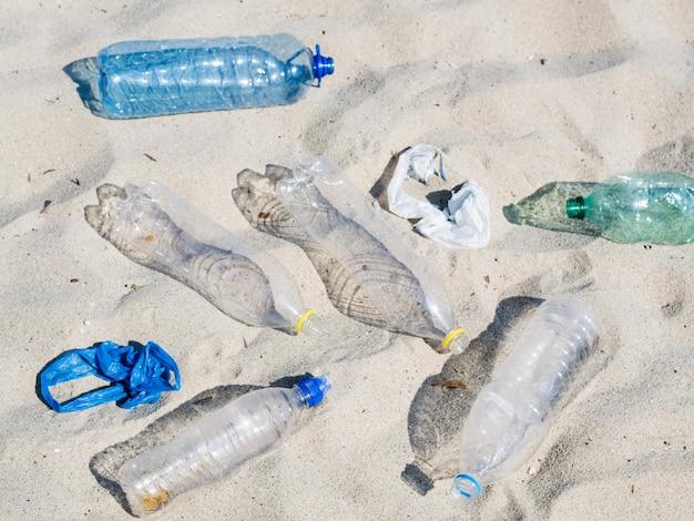 Leere plastikwasserflaschen und plastiktasche auf sand