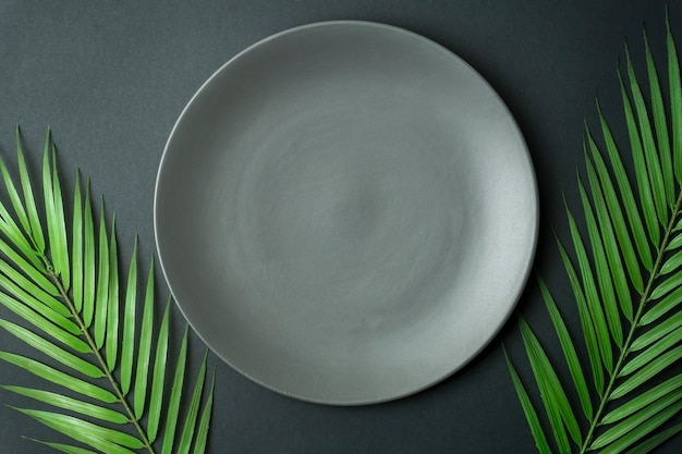 Leere platte auf dunklem hintergrund. leere graue keramikplatte für essen und abendessen auf einem dunklen schönen hintergrund.
