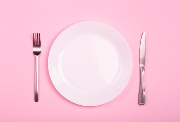 Leere platte auf einem rosa hintergrund. weißer teller mit messer und gabel auf einem rosa leeren tisch.