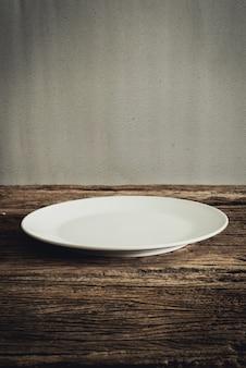 Leere platte auf hölzerner tischplatte