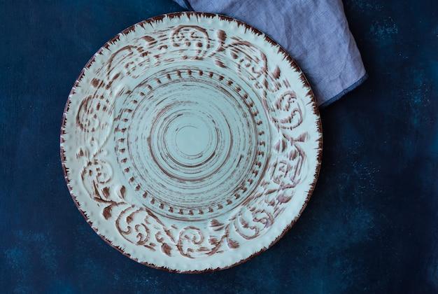 Leere platte der bläulichen weinlese, leinenserviette auf dunkelblaue konkrete tischplatte, flache lage