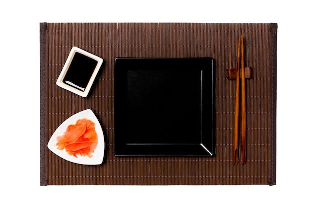 Leere platte des schwarzen quadrats mit essstäbchen für sushi