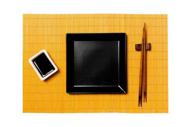 Leere platte des schwarzen quadrats mit essstäbchen