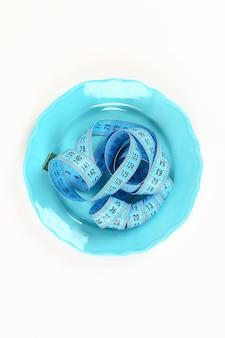 Leere platte mit blauem maßband. diät essen gewichtsverlust konzept.
