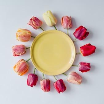 Leere platte mit kreativer anordnung von tulpenblumen auf heller wand. flach liegen.