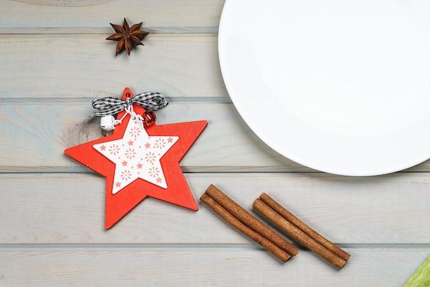 Leere platte mit weihnachts- und neujahrsdekoration für das feiertagsmenü.