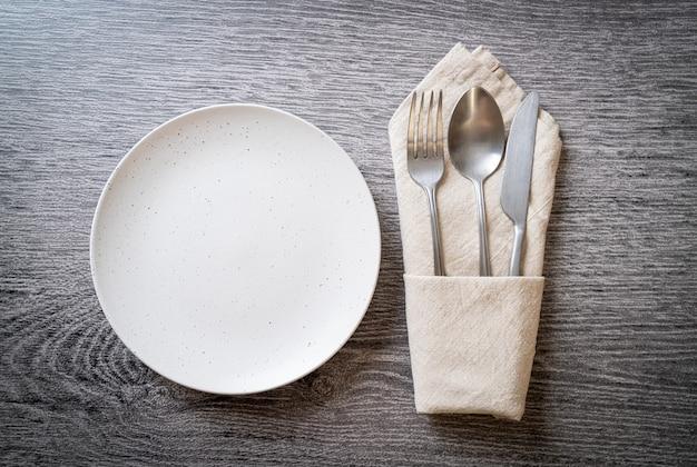 Leere platte oder schale mit messer, gabel und löffel auf holzfliesenhintergrund