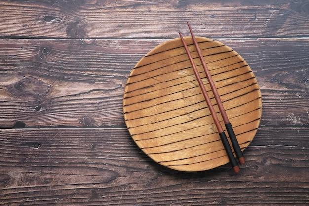Leere platte und stäbchen auf hölzernem backgroun.