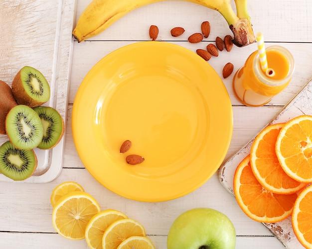 Leere platte und verschiedene früchte herum