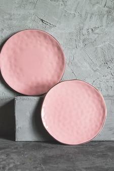 Leere platten (keramik) auf grauem steinhintergrund. graues minimalismuskonzept