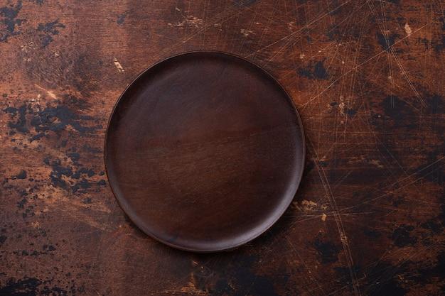 Leere platten- und leinenserviette auf braunem hölzernem hintergrund