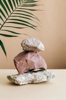 Leere podium stones turm auf braunem kraftpapier hintergrund. stones-sockelanzeige auf beigefarbenem hintergrund aus muschelsteinen palmblatt. abstraktes hintergrundmodell für die produktpräsentation.