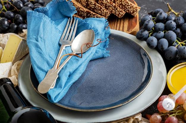 Leere portion blaue platte mit gabel löffel im rahmen von lebensmittelzutaten mediterrane küche gastronomie vorspeise snacks trauben käse wein. kopieren sie platz oder vorlage auf blauem teller.