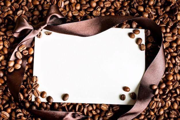 Leere postkarte auf gerösteten kaffeebohnen