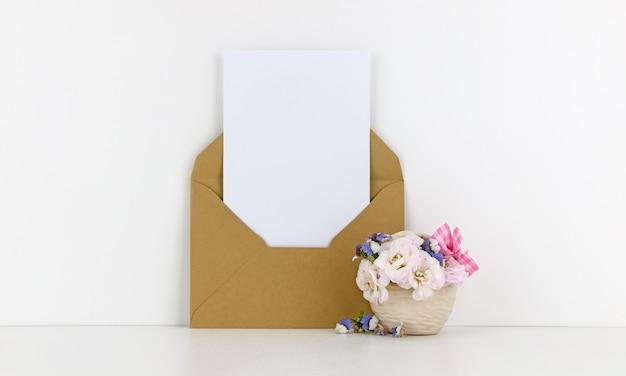 Leere postkarte mit kraftpapierumschlag und weißen blumen
