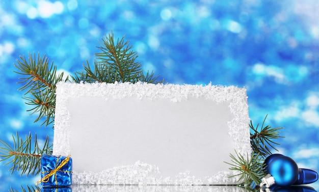 Leere postkarte, weihnachtskugeln und tannenbaum auf blauem hintergrund