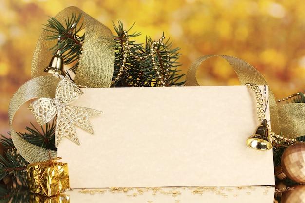 Leere postkarte, weihnachtskugeln und tannenbaum auf gelber fläche