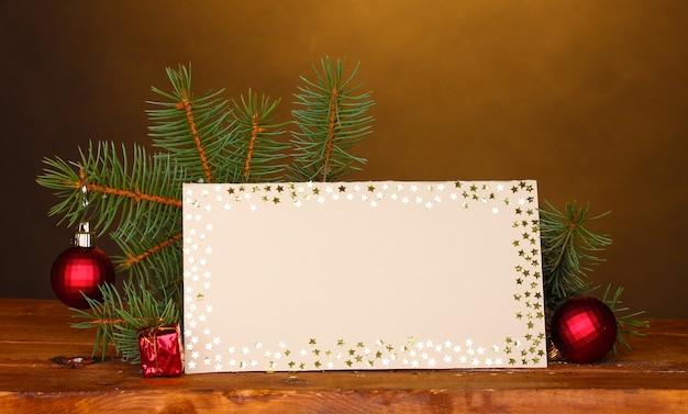 Leere postkarte, weihnachtskugeln und tannenbaum auf holztisch auf braunem hintergrund