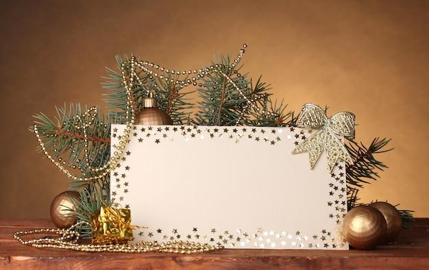 Leere postkarte, weihnachtskugeln und tannenbaum auf holztisch auf brauner oberfläche