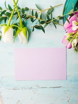 Leere purpurrote karte blüht tulpenrosenfrühlingspastellfarbhintergrund mit copyspace.