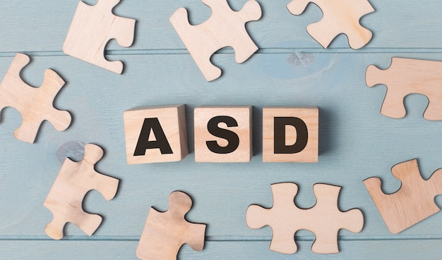 Leere puzzles und holzwürfel mit dem text asd autism spectrum disorder liegen auf hellblauem hintergrund.