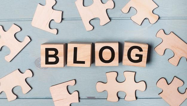 Leere puzzles und holzwürfel mit dem text blog liegen auf blauem hintergrund.