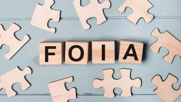 Leere puzzles und holzwürfel mit dem text foia the freedom of information act liegen auf einem hellblauen hintergrund.