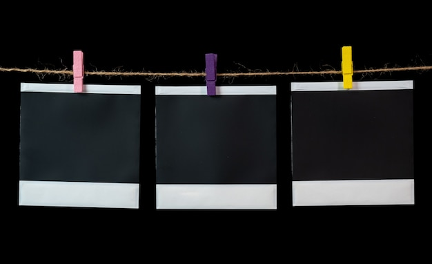 Leere quadratische bilderrahmen, die an einer wäscheleine hängen leere quadratische bilderrahmen