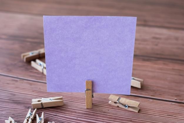 Leere quadratische notiz, umgeben von wäscheklammern, die eine neue bedeutung zeigen, leeres stück klebriges papier
