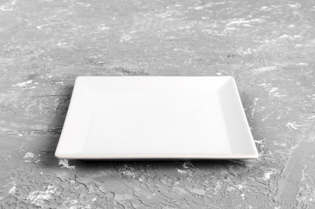Leere quadratische platte auf zementhintergrund. perspektivische ansicht