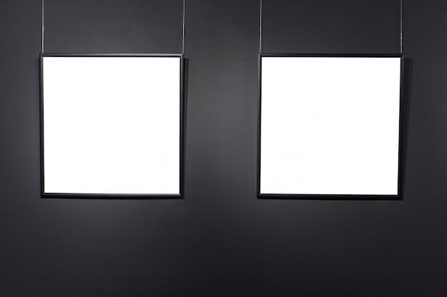 Leere quadratische rahmen auf schwarzer backsteinmauer. leere raumplakate oder kunstrahmen warten darauf, gefüllt zu werden. quadratischer schwarzer rahmenhintergrund