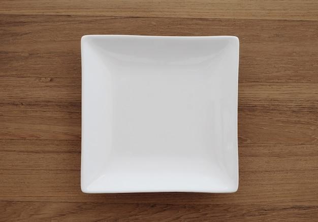 Leere quadratische weiße platte im hölzernen hintergrund