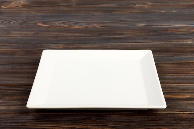 Leere quadratische weiße platte im holz, lebensmittelanzeigenmontage. perspektivische ansicht