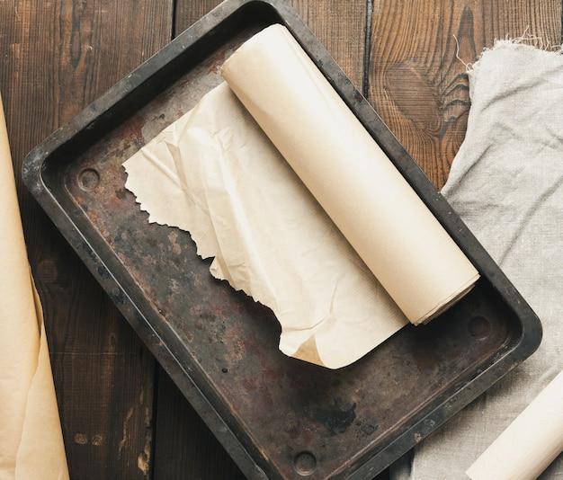 Leere rechteckige metallpfanne bedeckt mit braunem pergamentpapier und papierrollen auf einem holztisch, draufsicht