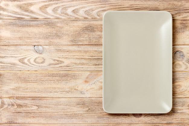 Leere rechteckige platte auf hölzernem. ansicht von oben