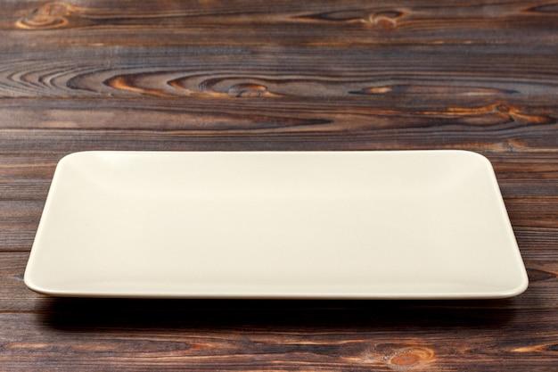 Leere rechteckige platte auf hölzernem hintergrund. ansicht von oben