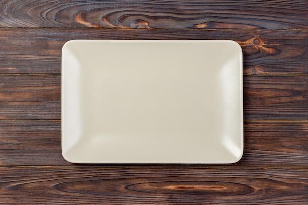 Leere rechteckige platte auf hölzernem hintergrund.