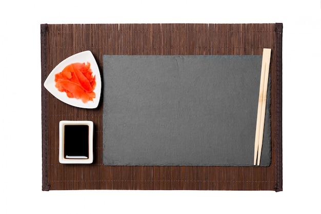 Leere rechteckige schwarze schieferplatte mit essstäbchen für sushi, ingwer und sojasoße an. draufsicht mit exemplar