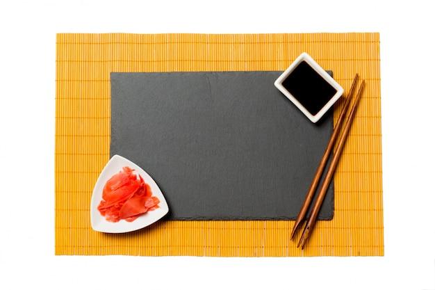 Leere rechteckige schwarze schieferplatte mit essstäbchen für sushi, ingwer und sojasoße auf gelbem bambusmattenhintergrund.